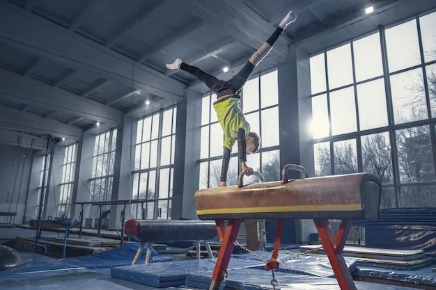 챔피언. 유연하고 활동적인 체육관에서 작은 남자 체조 훈련