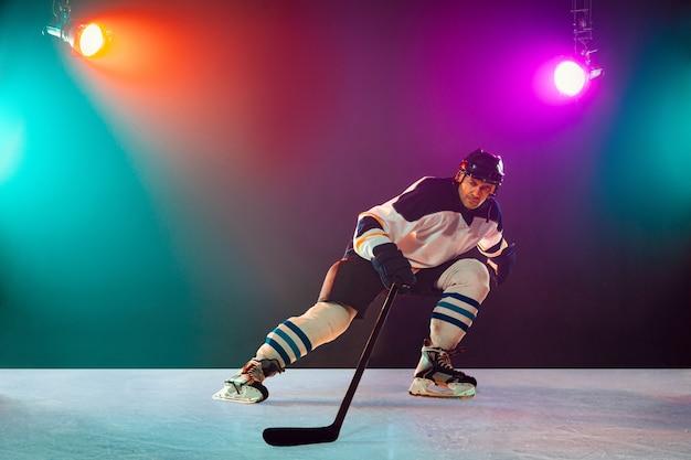 チャンピオン。アイスコートの男性ホッケー選手と懐中電灯と暗いネオン色の背景。装備のスポーツマン、ヘルメットの練習。スポーツ、健康的なライフスタイル、動き、健康、行動の概念。