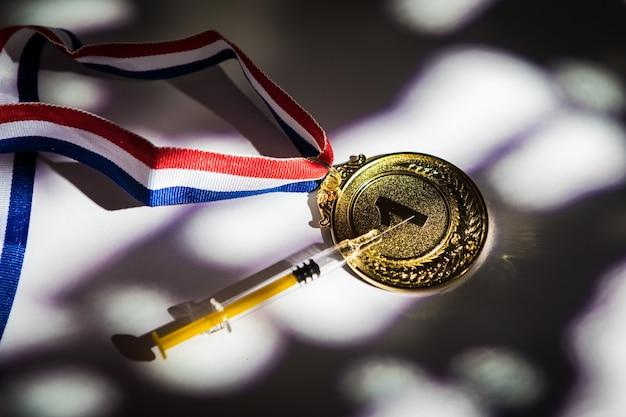 Золотая медаль чемпиона и шприц с допингом со светом и тенями, проникающими в окно. концепция спорта и допинга