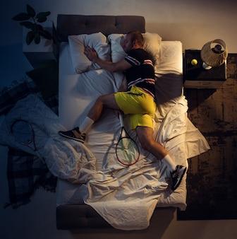 Чемпион. вид сверху на молодого профессионального теннисиста, спящего в своей спальне в спортивной одежде с ракеткой. любить спорт даже больше, чем комфорт, смотреть матч даже во время отдыха. действие, движение, юмор.