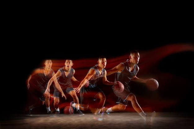 Чемпион. молодой восточноазиатский баскетболист в действии и движении, прыгающий в смешанном стробоскопическом свете на темном фоне студии. понятие спорта, движения, энергии и динамичного, здорового образа жизни.