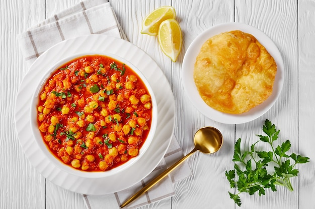 Chana masala or chickpea curry with spices, tomato sauce, served on a white plate with indian fried bread bhatura