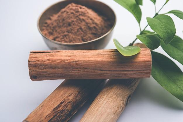 Чандан или порошок сандалового дерева с палочками и зелеными листьями