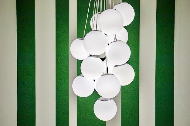 Люстра в виде множества круглых плафонов из шаров на фоне полосатых обоев.