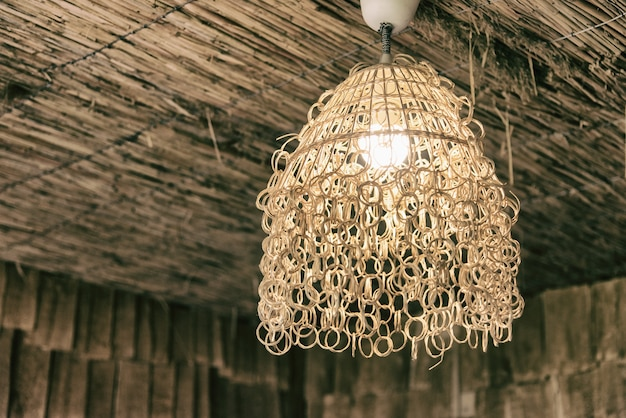 Chandelier made of straws on wooden ceiling