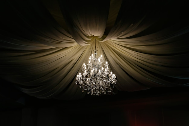 Chandelier surrounded by waveshaped curtains