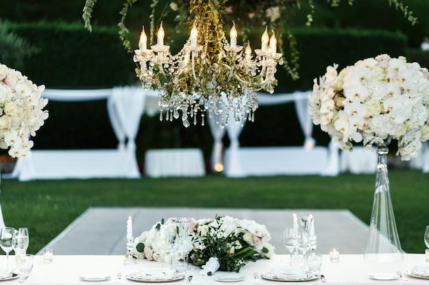 꽃과 녹지와 샹들리에 저녁 식사 테이블 위에 달려
