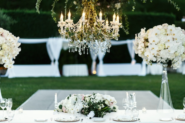 Chandelier with flowers and greenery hangs over dinner table