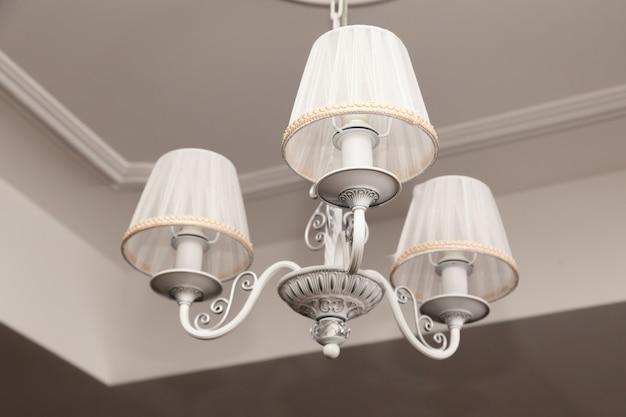 천장에 매달려있는 3 개의 전기 램프와 전등 갓이있는 샹들리에
