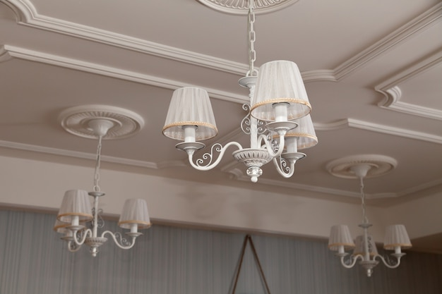 Chandeliers with three electric lamps and lampshades hanging on the ceiling