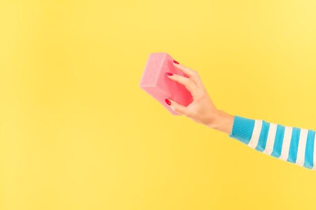 コンセプトを変更します。スポンジで架空のエラーを消去する女性の手。黄色の背景にスペースをコピーします。