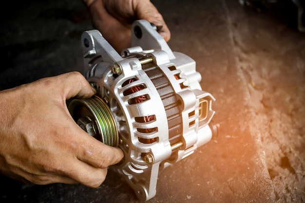 Change new car alternator with hand in the garage or auto repair service center.