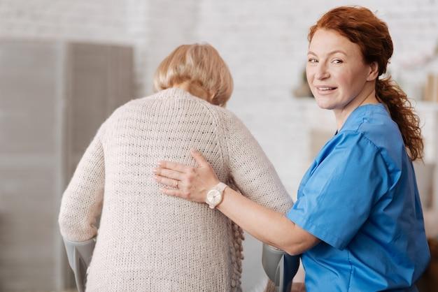 世代交代。資格のある優しい専門看護師が年配の女性を訪問し、彼女が元気であることを確認しながら彼女と一緒に歩いている