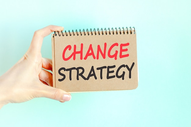 Change strategy word inscription on card paper sheet in hands of a businesswoman. black letters on white paper