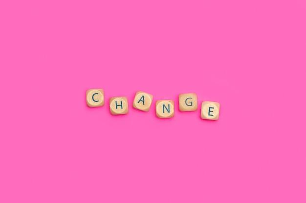 Изменить слово из деревянных блоков букв на розовом фоне