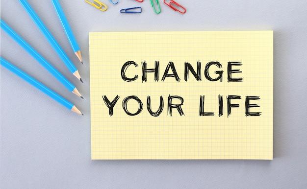 연필과 종이 클립 옆의 회색 표면에 노트북의 인생 텍스트를 변경하십시오.
