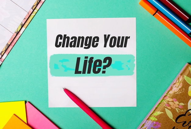 Change your life written on a turquoise surface near bright stickers, notepads and markers.