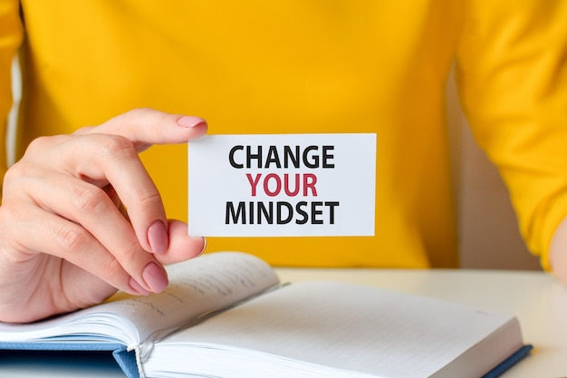 Change your mindset is written on a white business card in a woman's hand