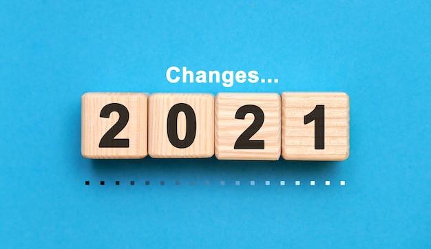 青い背景の木製の立方体で2021年を変更します