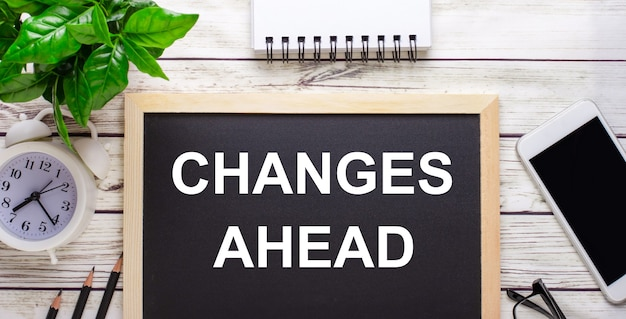 鉛筆、スマートフォン、白いメモ帳、鉢植えの緑の植物の近くの黒い背景に書かれた変更先