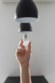 Changing the bulb for led bulb in floor lamp in black colour. on light gray background