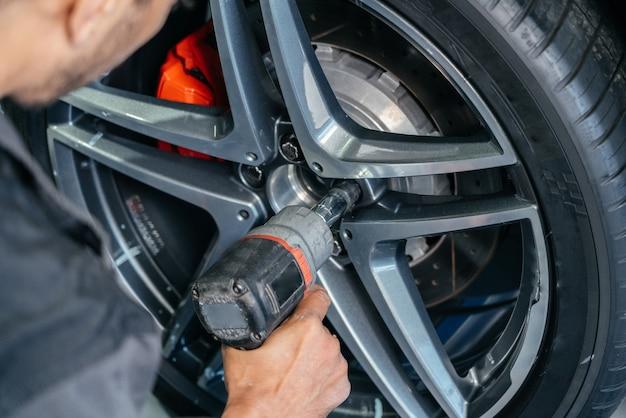 볼트 개념을 풀기 위해 전기 드릴을 사용하여 자동차 수리점에서 자동차 휠 교체