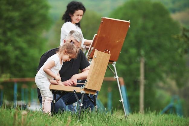 Cambiare i colori. nonna e nonno si divertono all'aperto con la nipote. concezione della pittura