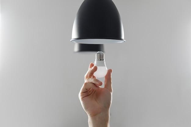 Замена лампочки на светодиодную в торшере черного цвета.