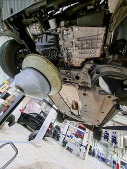 車のエンジンのオイルを交換します。車の下からの眺め