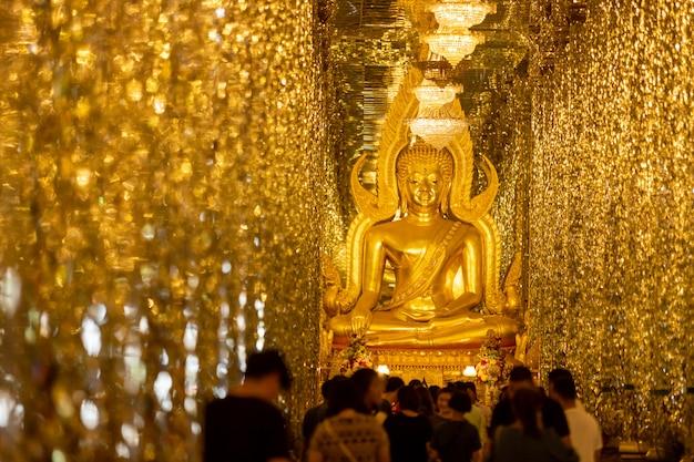 Chantaram temple or tha sung temple, beautiful golden buddha statue inside wihan kaeo or glass sanctuary, famous place in uthai thani, thailand.