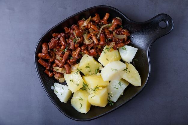 작은 검은 팬에 삶은 감자, 양파, 딜, 기름을 넣은 살구 버섯. 전통적인 러시아 요리입니다. 검정색 배경, 클로즈업, 카메라 줌.