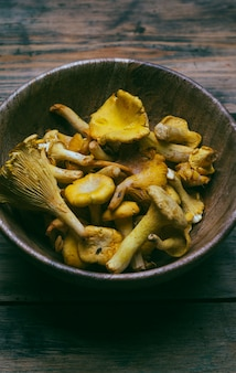 Chanterelle mushrooms on a wooden background. raw mushrooms in a wooden bowl.