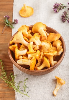 Chanterelle mushrooms in wooden bowl and spice herbs with linen textile, side view.
