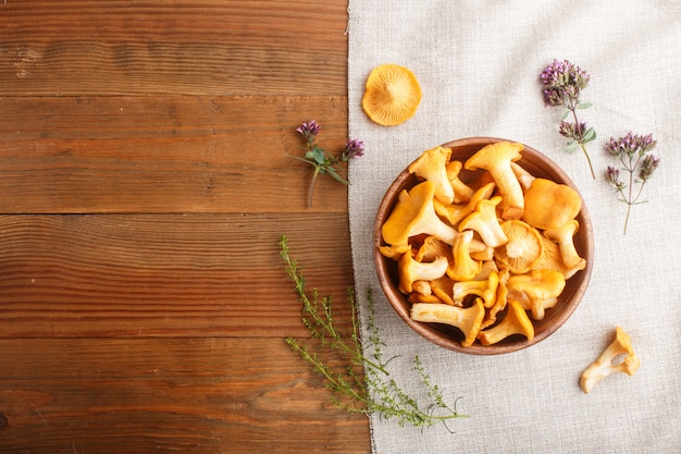 Chanterelle mushrooms in wooden bowl and spice herbs with linen textile. top view.