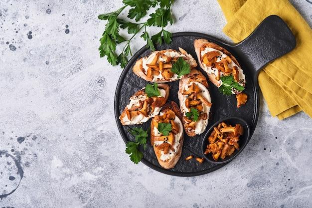 アンズタケのチーズサンドイッチ。古い木製の背景にクリーミーなチーズ、調味料、コショウ、新鮮なパセリのオープンサンドイッチ。モックアップ。上面図。
