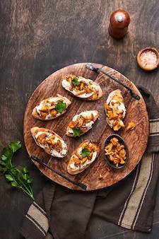 アンズタケのチーズサンドイッチ。古い木製の背景にクリーミーなチーズ、調味料、コショウ、新鮮なパセリのオープンサンドイッチ。モックアップ。上面図。 Premium写真