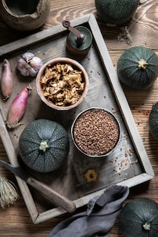 Ingredienti di zucchine rotonde ripiene di gallinacci su scatola di legno
