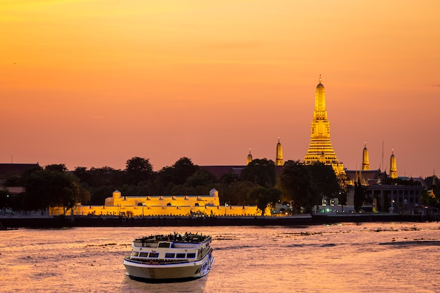Chao phraya river cruise boat with temple of the dawn at sunset