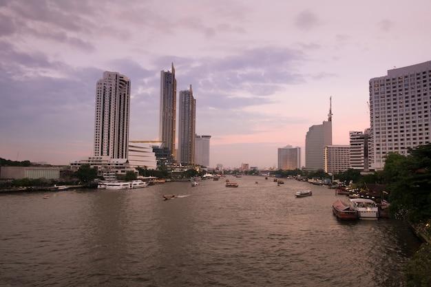 Благоустраивайте взгляд захода солнца на реке chao phraya с целью шлюпок и современных зданий вдоль берега реки.
