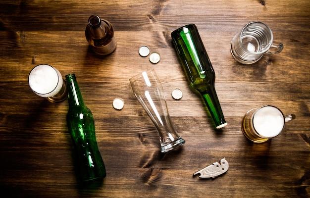 木製のテーブルの上のカオスビール。ビールのボトルとグラス。