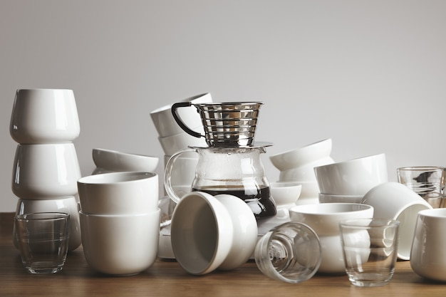 두꺼운 나무 테이블에 카오스 빈 흰색과 투명 커피 컵. 중앙에 여과 된 음료가있는 드립 커피 메이커.