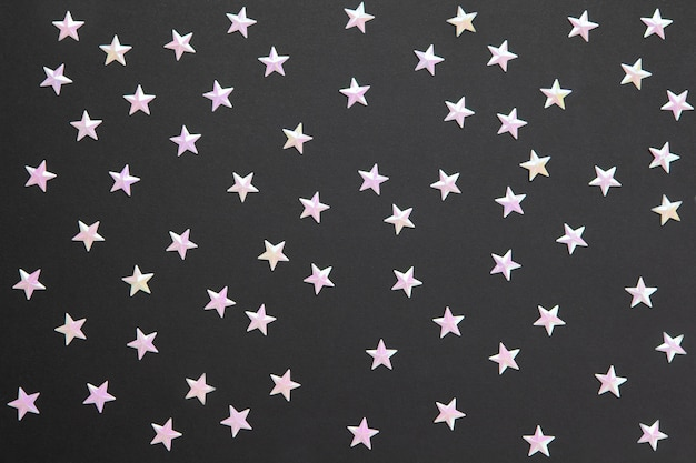 Chaotic pattern from numerous pearl confetti in form of small stars on black paper background. celebration, holidays, sales, fashion