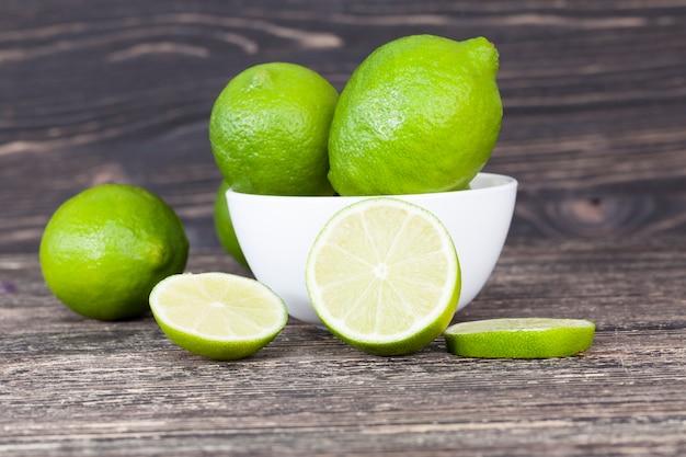 テーブルの上に無秩序に散らばっている緑の熟した酸っぱいライム、果物が横たわっているボウルのある黒い背景、1つのライムが刻まれています