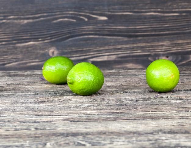 テーブルに無秩序に散らばっている緑の熟した酸っぱいライム、黒の背景