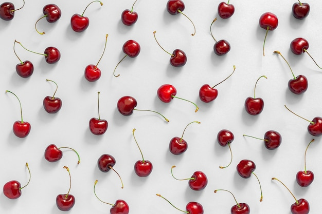 Chaotically scattered red ripe sweet cherry on grey background, texture top view, flat lay