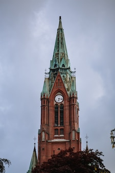 The chapel building is made of red brick with a green dome