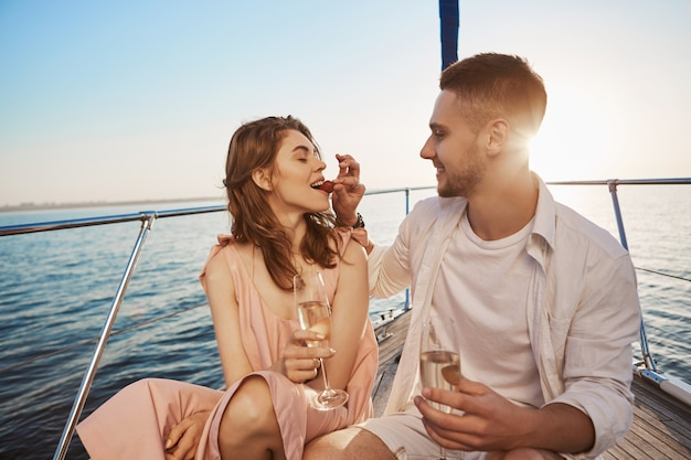 Привлекательные европейские пары на летние каникулы, наслаждаясь парусным спортом на борту яхты, пить chapmaign. парень пообещал ей провести отпуск вместе, поэтому он купил лодочный тур.