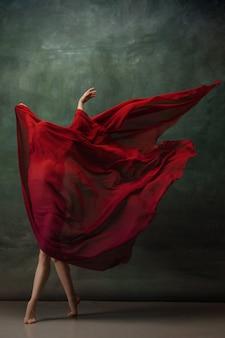 キャラクター。暗いスタジオの背景で踊る優雅な古典的なバレリーナ。真っ赤な布。優雅さ、芸術家、動き、行動、動きの概念。無重力で柔軟に見えます。ファッションスタイル。