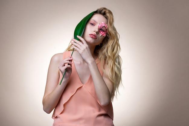 花のキャラクター。ピンクのメイクと花のキャラクターでポーズをとる長いウェーブのかかった髪のモデル