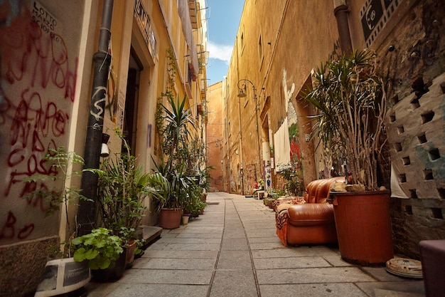Characteristic alley of the city of cagliari in sardinia with an outdoor sofa